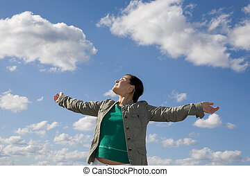 freedom woman - attractive brunette woman relaxing on sky...