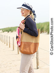 Happy older woman smiling at the beach