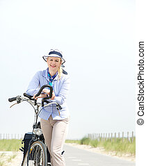 Happy mature woman relaxing with bike on a summer day -...