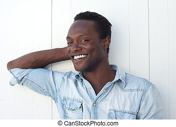 Happy young black man smiling against white background...