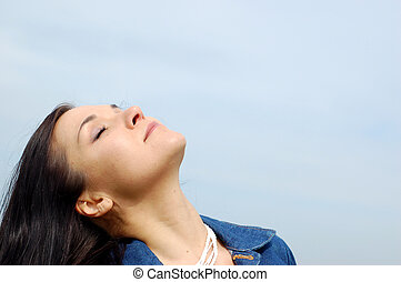 freedom - attractive brunette woman on sky background