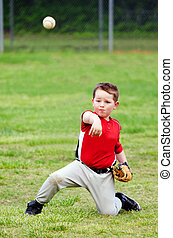 Child in uniform throwing baseball