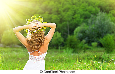 beautiful woman in a wreath of flowers on nature
