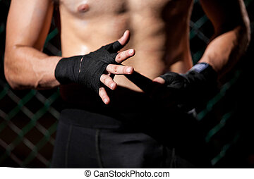 Hand Wrap in a fighting cage - Closeup of a mixed martial...