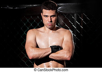 MMA Fighter in a fighting cage - Portrait of a Latin mixed...