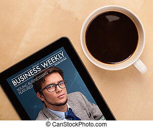 Workplace with tablet pc showing magazine cover and a cup of...