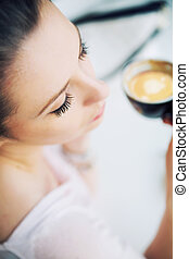 Nice picture of resting brunette woman holding a cup of coffee
