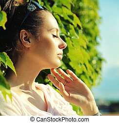 Attractive young woman leaning on plant fence