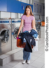 Upset Woman Holding Basket Full Of Dirty Clothes - Portrait...