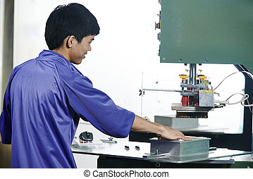 chinese worker operating press in china production factory...