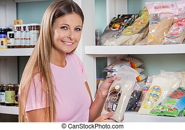 Woman Holding Food Packet In Grocery Store - Portrait of...