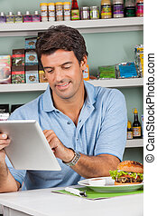 Male Customer With Snacks Using Digital Tablet In Store