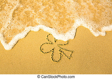 Clover leaf (concept: St. Patrick Day) - written in sand on...