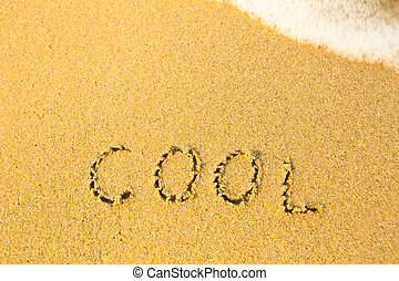 Cool - written in sand on beach texture