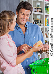 Woman Showing Cheese To Man In Supermarket - Young woman...