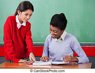 Schoolgirl Asking Question To Female Teacher At Desk -...