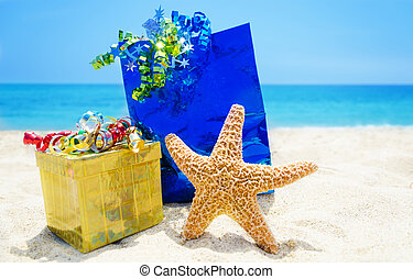 Starfish with gifts on the beach - holiday concept