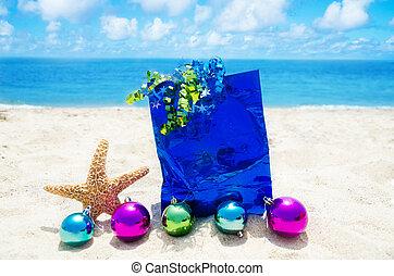 Starfish with Christmas balls and gift bag on the beach