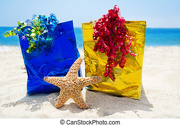 Starfish with gift bags on the beach - holiday concept