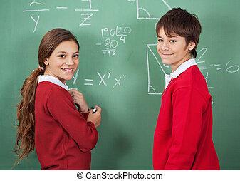 Portrait Of Teenage School Students Standing Against Board -...