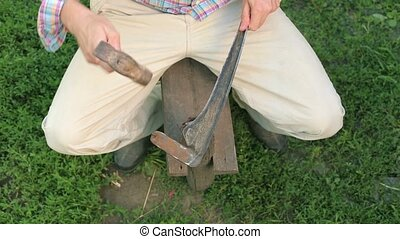 Man rivet plait - farmer sharpening his scythe