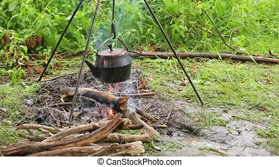 Kettle on the fire - kettle on fire in a camping
