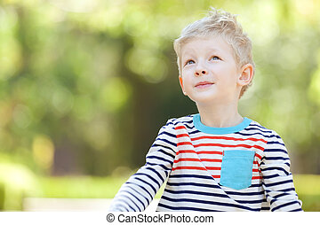 boy outdoors - thoughtful cute positive boy outdoors, green...