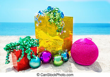 Gifts with Christmas ball on the beach