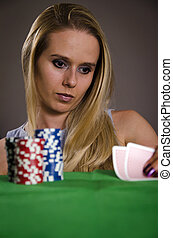 woman playing poker lifting her cards thinking about the...