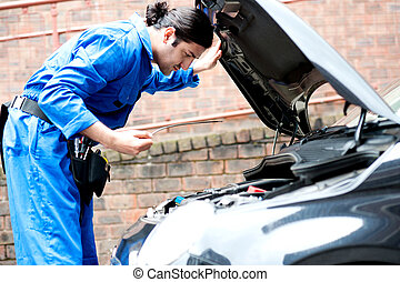 Mechanic checking the motor oil of the car