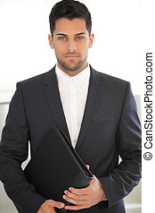 Serious young businessman with a folder