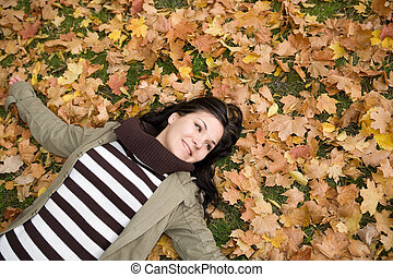 happy autumn - attractive brunette woman lying on leaves