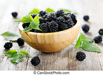 Blackberries with leaves on wooden table
