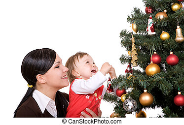 happy family - happy mother and daughter over christmas tree