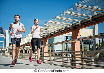 Jogging together - Young sport couple running together in...