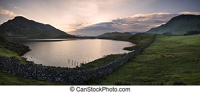 Panorama of beautiful sunrise reflected in calm Cregennen Lakes in Snowdonia National Park
