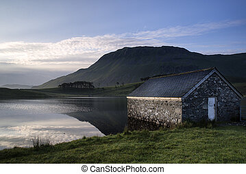 Stone boat shed and mountain reflected in lake at sunrise -...