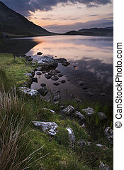 Beautiful sunrise reflected in calm Cregennen Lakes in Snowdonia National Park
