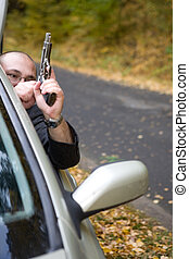 man with gun - danger gangster traveling by car