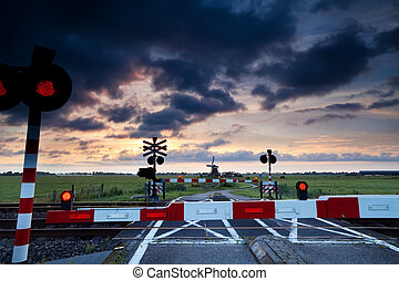 closed rail crossing at sunrise and windmill - closed rail...