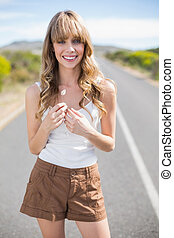 Smiling pretty woman holding flower while walking on the...