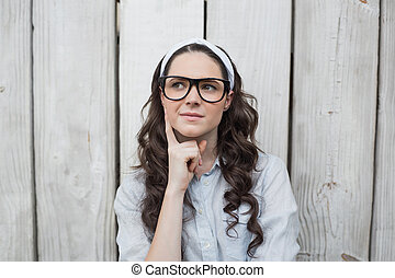 Pensive trendy woman with stylish glasses posing on wooden...