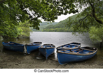 Old fashioned retro style rowing boats on shore of lake in Summe
