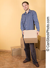 moving in - happy man with boxes moving in
