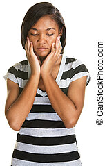 Sad Teen Looking Down - Sad teenager holding her face and...