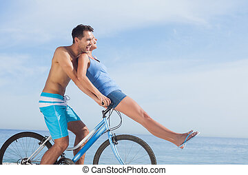Man giving girlfriend a lift on his crossbar of bike on the...