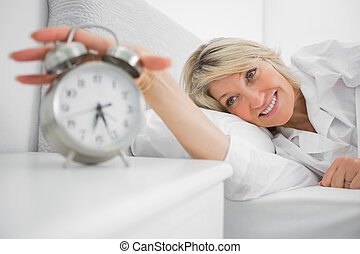 Blonde woman turning off ringing alarm clock lying in bed at...