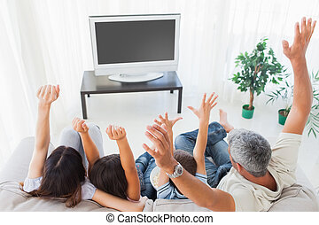 Family raising their arms in front of television at home