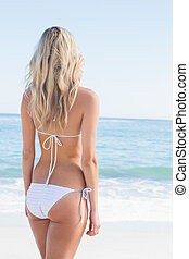 Beautiful blonde in white bikini looking at the sea at the...