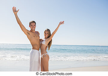 Happy couple smiling at camera and waving on the beach
